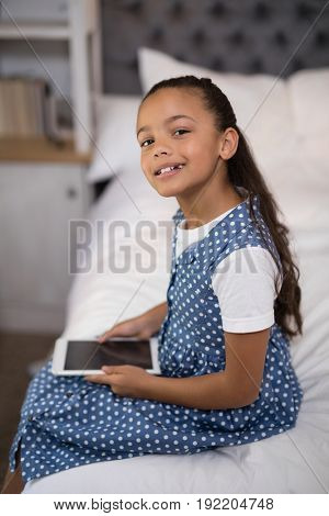 Portrait of smiling girl holding digital tablet while sitting on bed at home