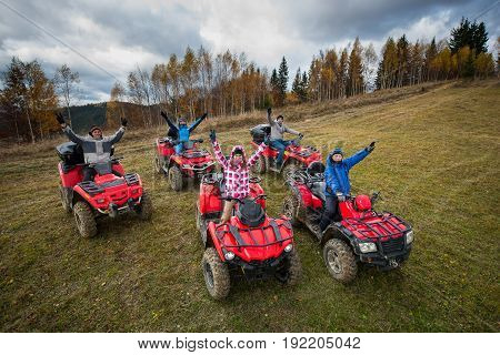 Young People In Winter Clothes With Raised Hands Up On Red Atv Off-road Vehicles On A Countryside Tr