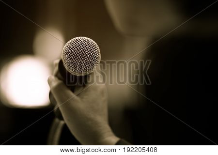 blurred of businessman hand holding microphone for speech presentation in conference hall vintage tone