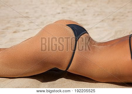 Summer beach concept. Sandy woman buttocks on the beach background. Sexy summer woman body. White sand of tropical beach. Vacation at Paradise. Ocean beach relax travel.