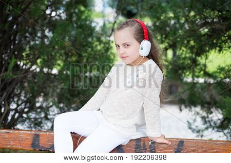 Pretty Little Girl Enjoying Music Using Headphones