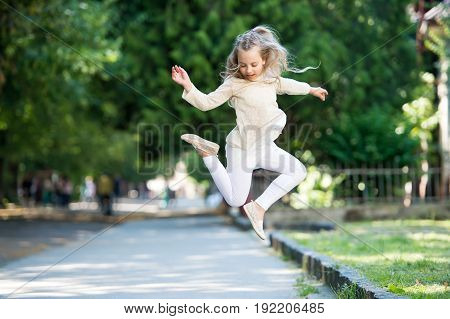 Pretty Little Girl With Curly Blonde Hair Jumping On Street