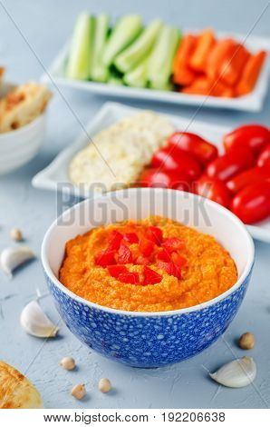 Red Bell pepper hummus with vegetables on a grey background