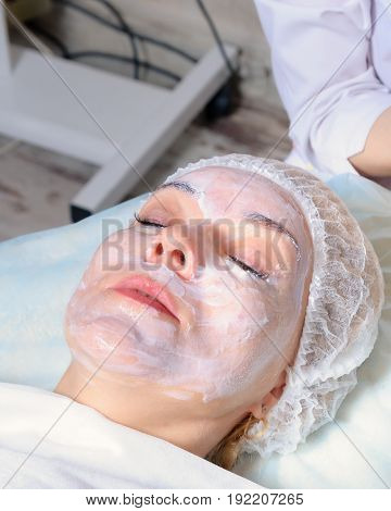The beautician prepares face girls cream anesthetic before beauty