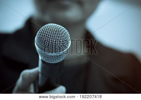blurred of businesswoman speech with microphone at presentation in a conference