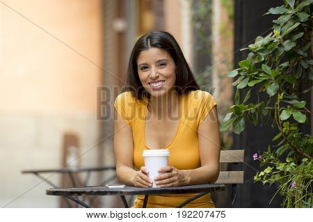 attractive latin woman in her twenties happy drinking coffee sitting outside a coffeeshop