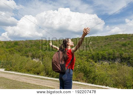 Young hiker girl standing over clouds landscape Travel Lifestyle concept adventure vacations outdoor happy emotions. Active hikers