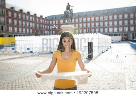 attractive latin woman on her twenties happy and excited in Plaza Major looking at a map.
