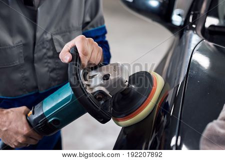 Close-up of hands worker using polisher to polish a black car body in the workshop. Detail of car care concept. The Black car in the garage. A man in a uniform