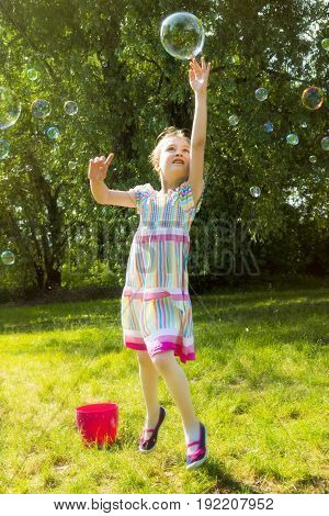 Little girl catching rainbow soap bubbles in summer park.