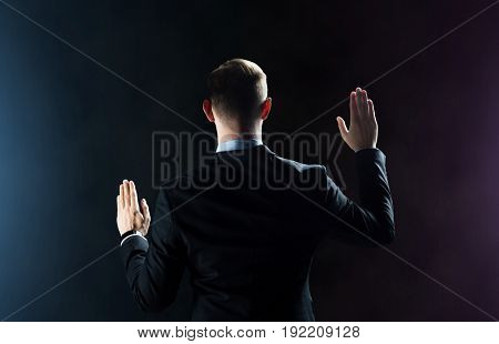 business, people, technology, cyberspace and virtual reality concept - businessman in suit something invisible over dark background