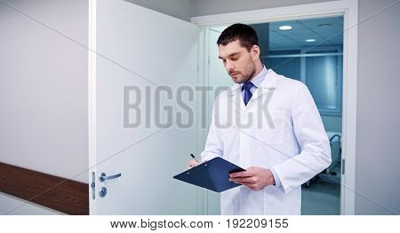 clinic, profession, people, health care and medicine concept - doctor with clipboard at hospital corridor