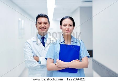 clinic, profession, people, health care and medicine concept - smiling medics or doctors with clipboard at hospital corridor