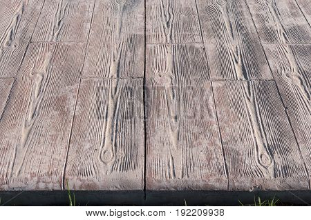 stamped concrete pavement close up detail expansion joint at middle, Wooden slats pattern, flooring exterior, decorative texture of cement paving with streaks of wood