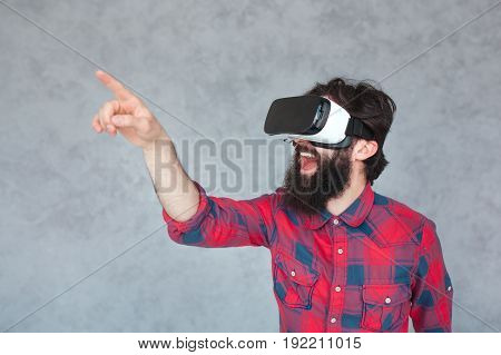 Horizontal studio shot of adult man wearing VR goggles touching air feeling excitement.