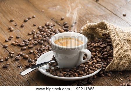 steaming cup of coffee with burlap sack and coffee beans on wooden table.
