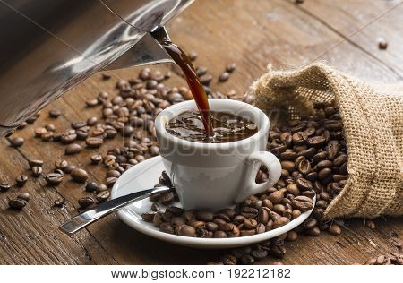 pouring coffee from coffeepot into white coffee cup.
