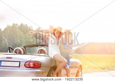 Woman showing something to female friend with map while leaning on convertible