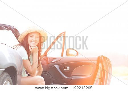 Happy woman sitting in convertible against clear sky