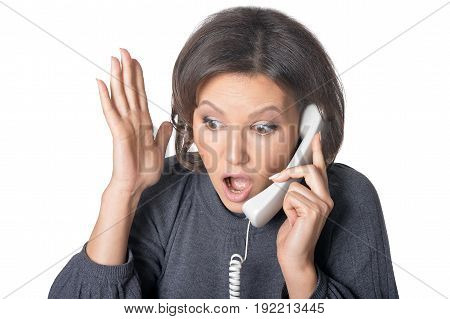 Emotional young woman screaming in handset isolated on white background