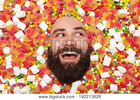 Close-up shot of bearded man lying in sweets and candies looking away happily.