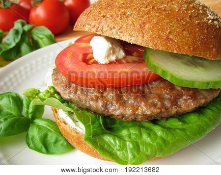Homemade rye burger wit meat, tomatoes, salad and cucumber