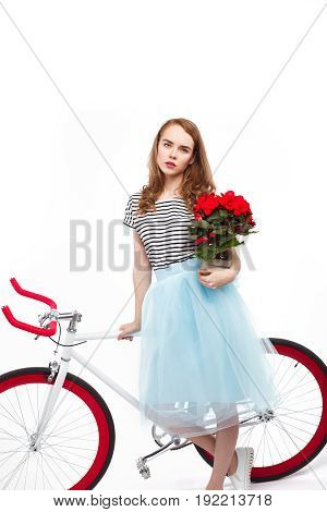 Young stylish woman holding flower pot and posing near colorful bicycle on white background.