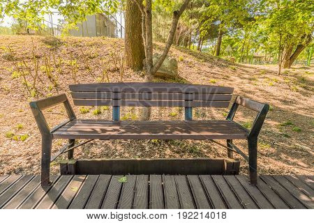 Park bench on a wooden walkway in a public park with tress and a power station in the background.