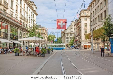 Zurich Shopping Street Bahnhofstrasse With Tram And Swiss Flag