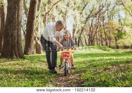 Mature man teaching little granddaughter how to ride bicycle in park