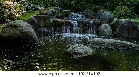Small waterfall streaming water into a pond surrounded by large boulders lush green foliage and flowers