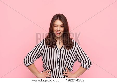 Pretty girl in striped shirt Licking lips and winking at camera on pink background.