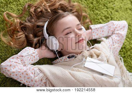 Cute little girl listening music with headphones