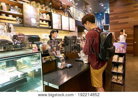 SEOUL, SOUTH KOREA - CIRCA MAY, 2017: man at Starbucks in Seoul. Starbucks Corporation is an American coffee company and coffeehouse chain.