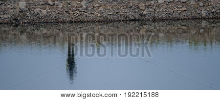 Abstract of a rocky riverbank on the far side of a river with the riverbank and a person reflection in the water