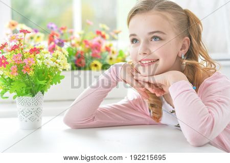 Pretty little girl sitting at table and holding hands on chin