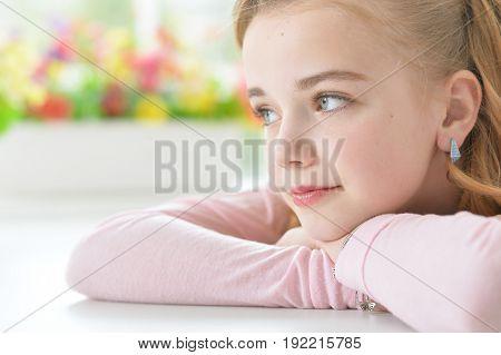 Cute little girl lying on folded arms