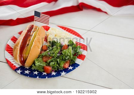 Close-up of American flag and hot dog on wooden table