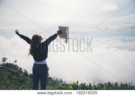 Women relax Read morning book good weather sky Mist. On the mountains the morning atmosphere.