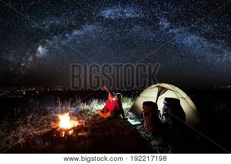 Night Camping Near The Town. Young Couple Sitting Near Campfire And Tent, Looking At Beautiful Night