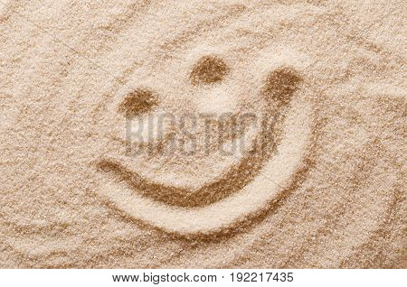 Happy smiling face in the sand. Eyes and mouth drawn with a finger in dry ocherous sand. Macro photo close up from above.