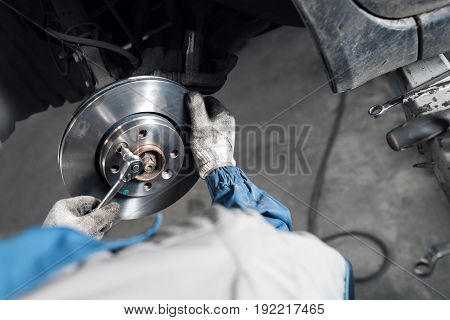 Car mechanic hands replace brakes in garage. Mechanic technician worker installing car wheel at maintenance. Worker changing brake disc. Brake disc installation concept. - can use to display or montage product or make a website for service