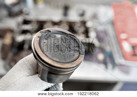 mechanic repairman at automobile car engine maintenance repair work. keep in hand the piston with carbon deposits. can use to display or montage product or make a website for service