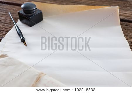 Ink pot, ink pen and legal documents arranged on wooden table