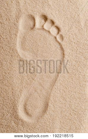 Footprint in the sand. Right foot footmark of of an adult in dry ocherous sand. Macro photo close up from above.