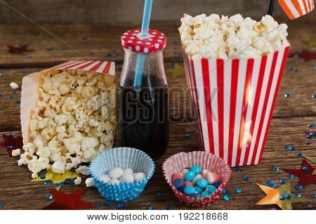 Popcorn, sweet food and cold drink decorated with 4th july theme on wooden table