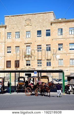 VALLETTA, MALTA - MARCH 30, 2017 - Horse drawn carriages in front of the Public Registry building Valletta Malta Europe, March 30, 2017.