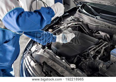 Mechanic checking oil level in a car workshop. can use to display or montage product or make a website for service