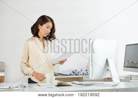 Portrait of young Vietnamese businesswoman reading document standing near office desk