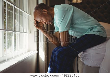 Side view of serious senior man sitting on bed by window at home